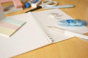 机の上のノートと筆記用具